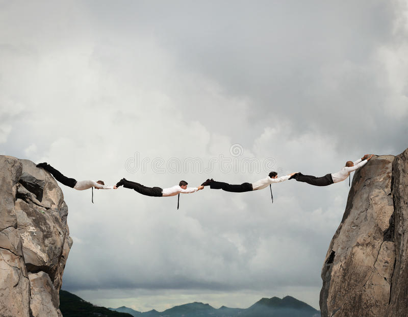 Business men bridge. Businessmen working together to form a bridge between two mountains stock photo