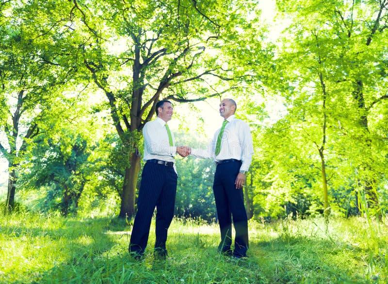 Business men handshaking in Garden stock photos