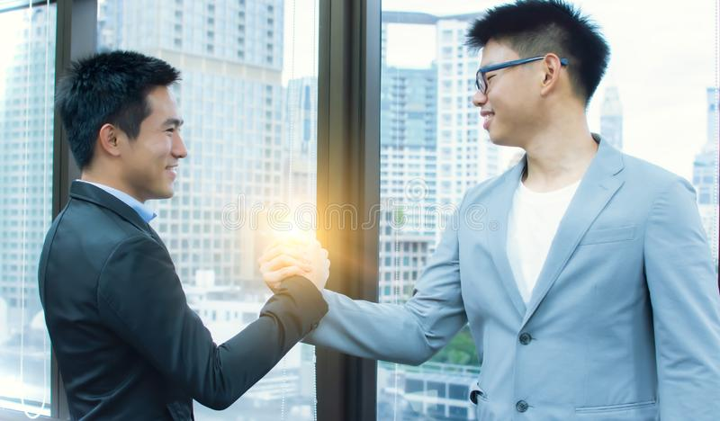 Business men making handshake for business agreement. Two Asian business men is making handshake for business dealing royalty free stock photo