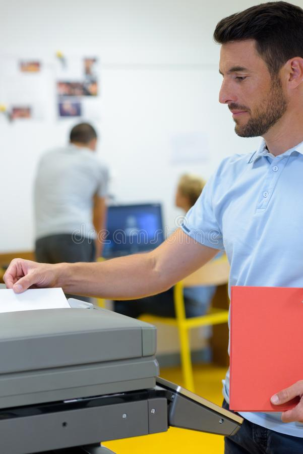 Business man making photocopy at photocopier. Business men making a photocopy at the photocopier stock images