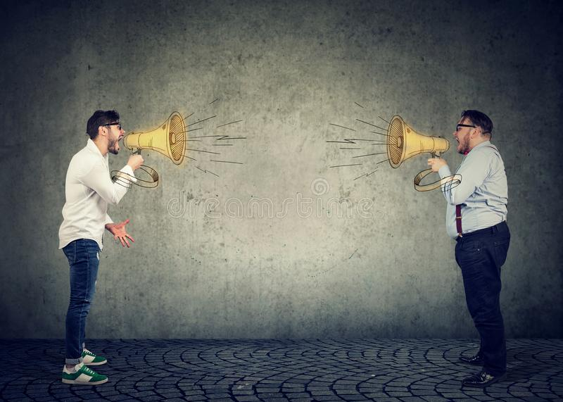 Business men screaming into a megaphone at each other royalty free stock photos