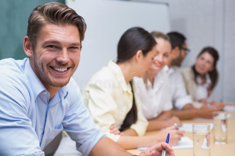 Business man smiling at camera with team behind him stock image