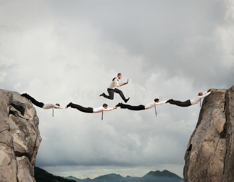 Business men support bridge. Businessmen working together to form a bridge between two mountains stock image