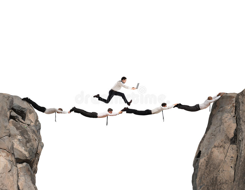 Business men support bridge. Businessmen working together to form a bridge between two mountains royalty free stock images