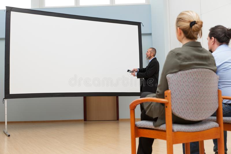 Business man with tablet in front of an canvas. Business men with tablet, maybe a coach is looking to an empty canvas stock image
