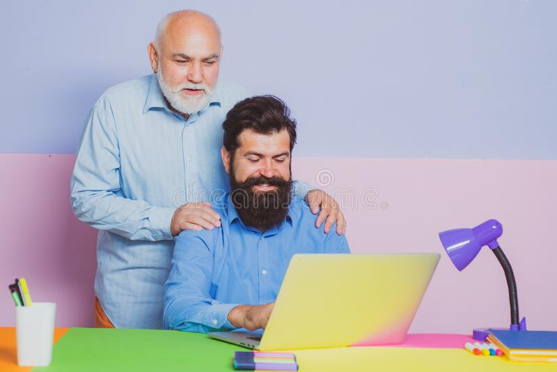 Business men team of two people talk and work together on laptop. Old father and young man looking at laptop screen. Watching movie or news in social network stock photos