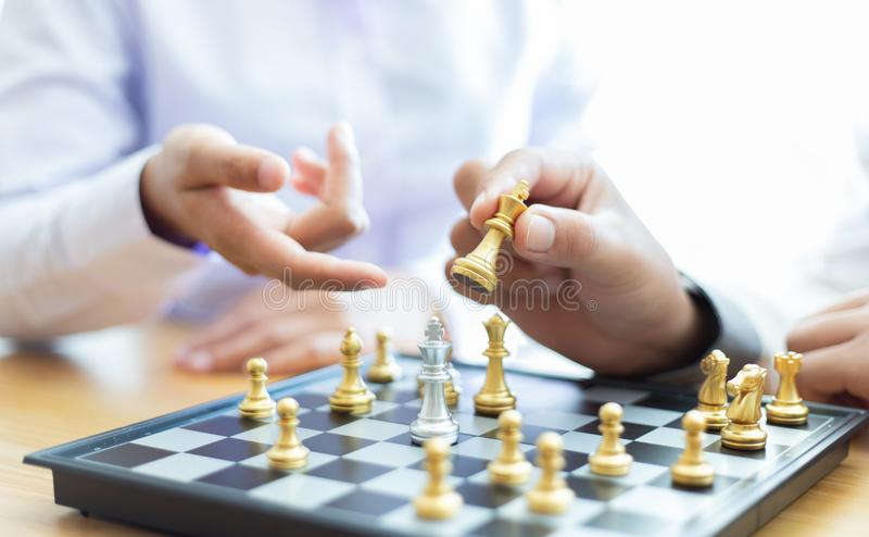 Business men and women analyze chess playing strategies to reduce risks and achieve success stock photos