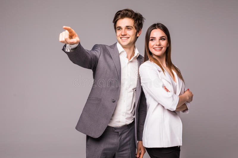 The business man and woman on a gray background. Man pointed away on gray royalty free stock images