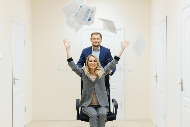 Business man and woman have fun in the office during a break. Business men and women have fun in the office during a break. People celebrate a successful deal royalty free stock photo