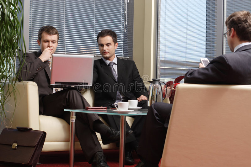Business men working in the office. Three young business men siting on leather sofa and working at laptop and palmtop in the office stock photo
