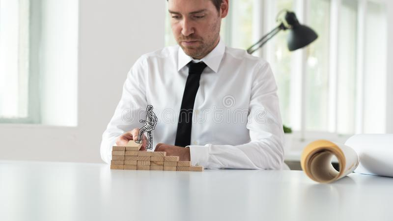 Business mentor assembling wooden steps for a silhouetted businessman royalty free stock photo