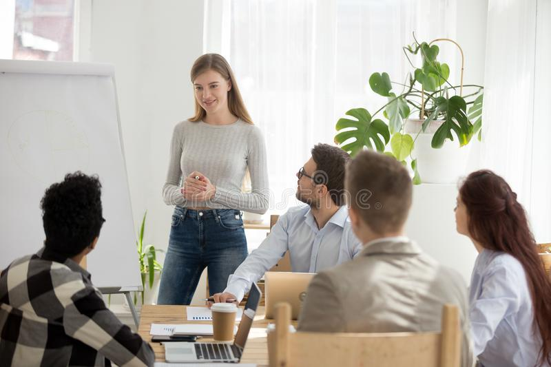 Business millennial team at seminar in office. Diverse businesspeople during seminar sitting in office. Millennial leader coach female standing near whiteboard royalty free stock photo