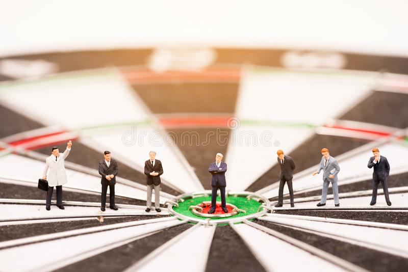 Business miniature people standing on dartboard. Business concept royalty free stock photos
