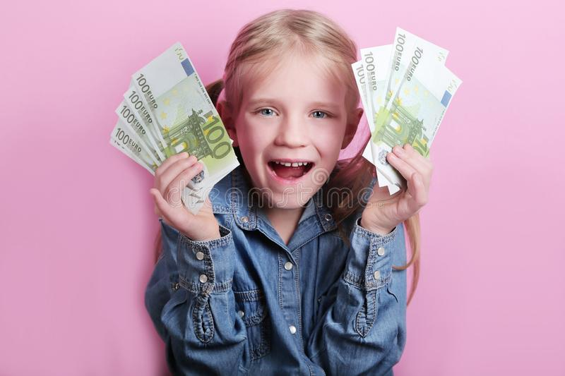 Business and money concept - happy little girl with euro cash money over pink background stock photo