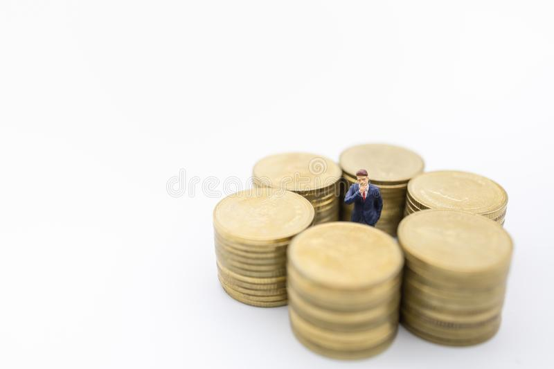 Business, Money, Finance and management concept. Close up of businessman miniature figure standing center of row of stack of gold. Coins on white background and royalty free stock image