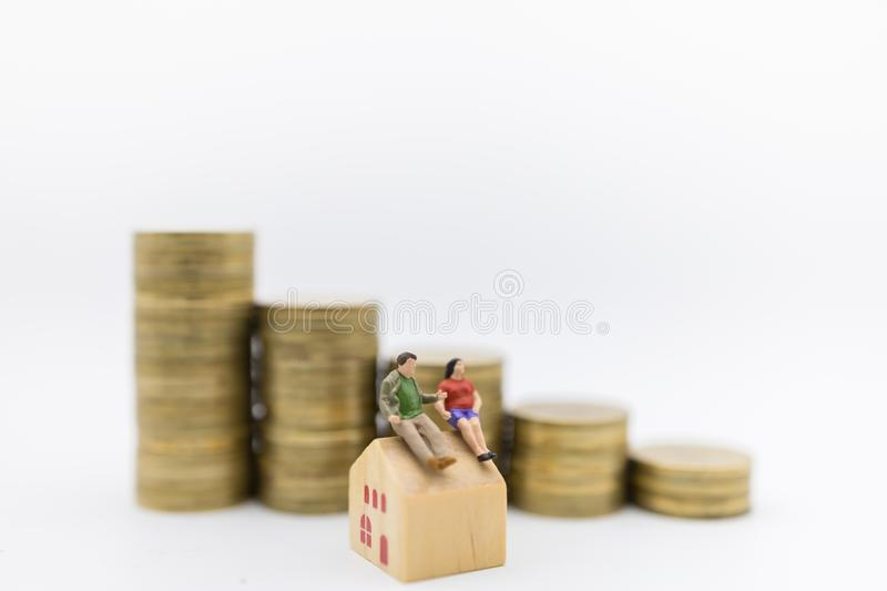 Business, Money and Home Loan Concept. Close up of couple fatman and woman miniature figure sitting on wooden house toy with stack. Of gold coin on white stock images