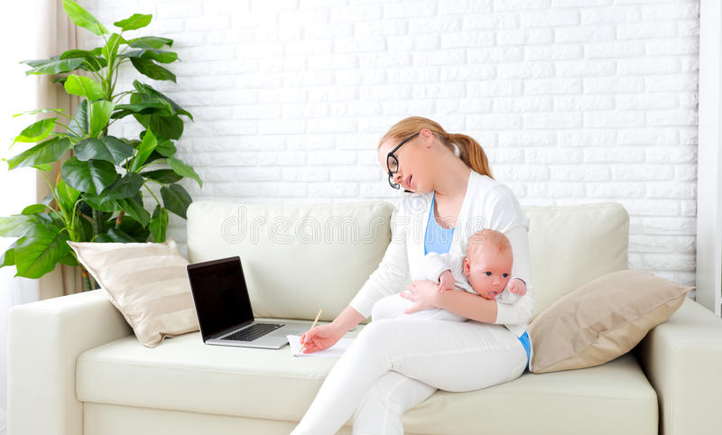 Business mother works at home via Internet with newborn baby. Business mother works at home via the Internet with newborn baby stock photography