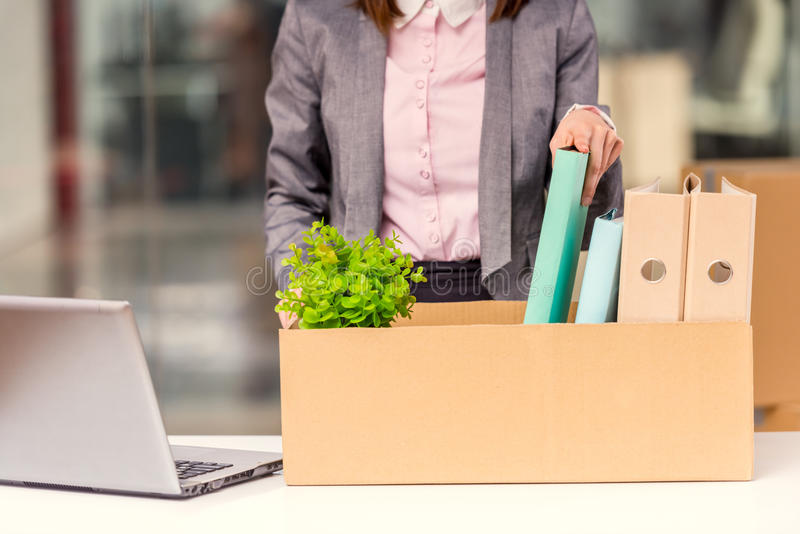 Business moving in office. Young happy business woman with boxes for moving into a new office stock photography