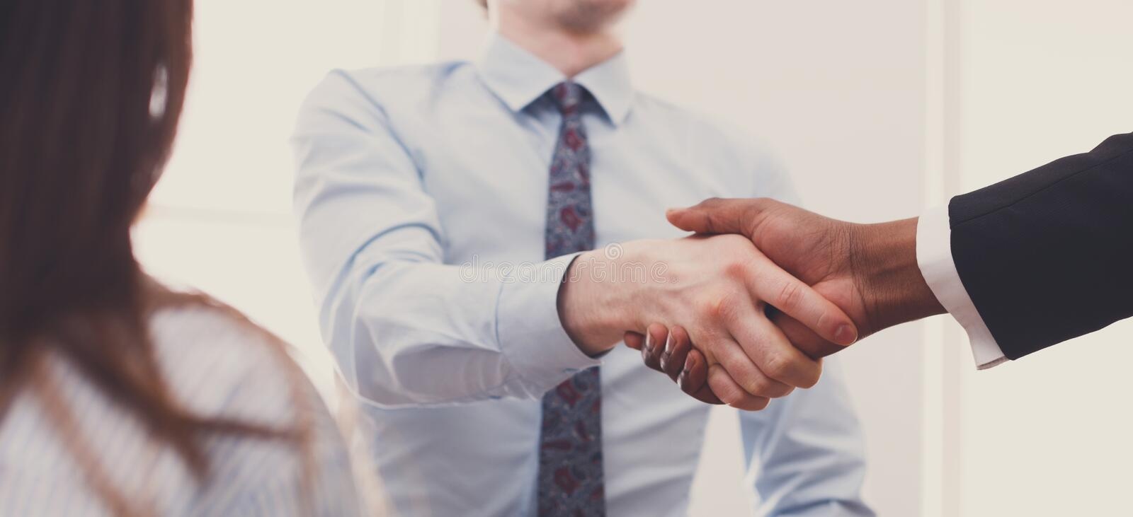 Business multiethnic handshake closeup at office meeting, contract conclusion royalty free stock photo