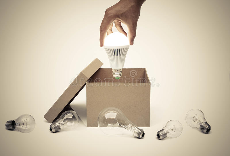 Business with new idea and innovation. Hand of a businessman holding a turned on LED light bulb coming out from a brown paper box surrounded by old incandescent stock image