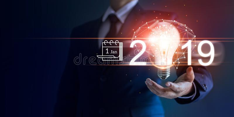 Businessman holding light bulb with icon on 2019. Business new year 2019. Businessman holding light bulb with icon business marketing and brain structure royalty free stock photo