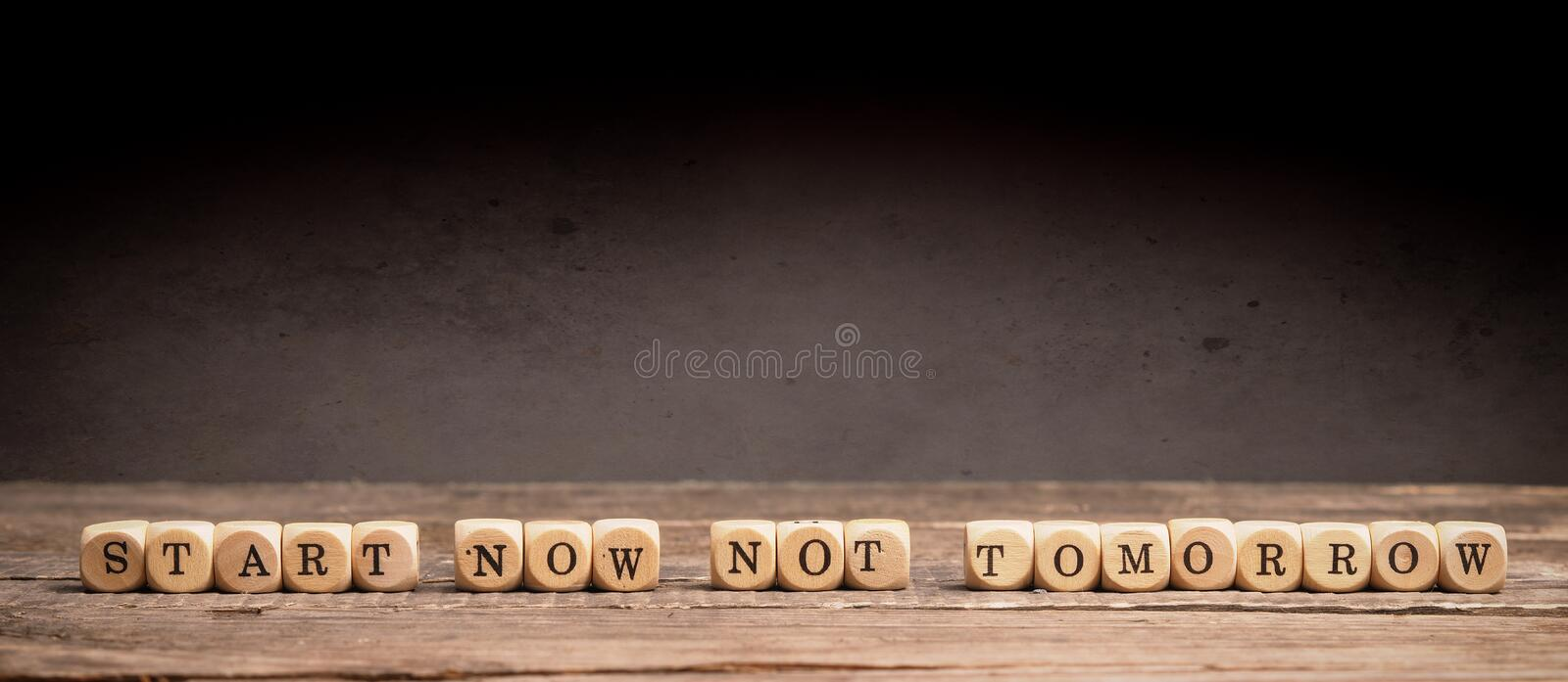 Start now, not tomorrow. Business or New Year resolution concept with small wooden dices and the words Start now not tomorrow royalty free stock image