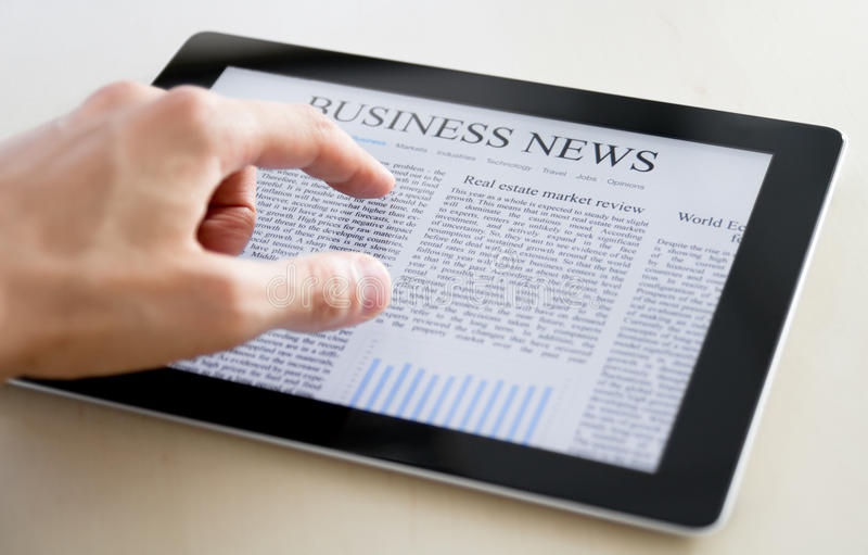Business News On Tablet PC. Man hands are pointing on touch screen device with business news