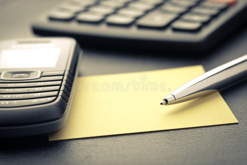 Business objects. A business desktop scene photographed up close. Focus on the tip of the pen and the mobile phone