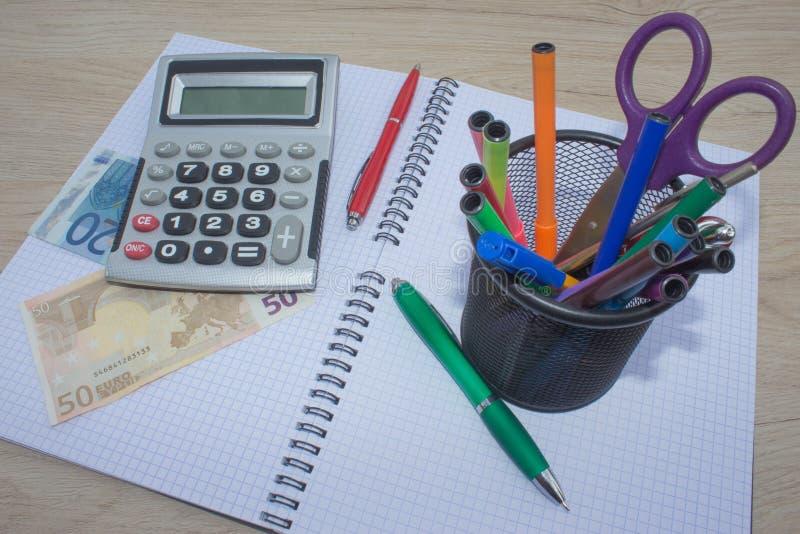 Business Objects im Büro im auf dem Tisch, Taschenrechner und in den Dollar auf Tabelle stockbilder