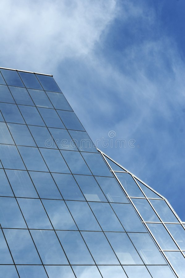 Business office. Glass office building with reflection of blue sky royalty free stock image