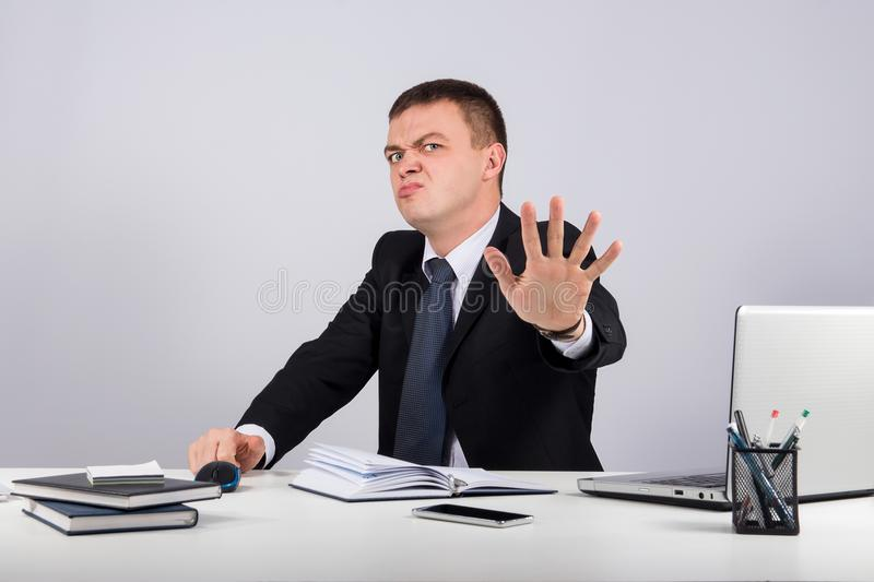 Funny buisnessman making stop gesture on gray background royalty free stock photography