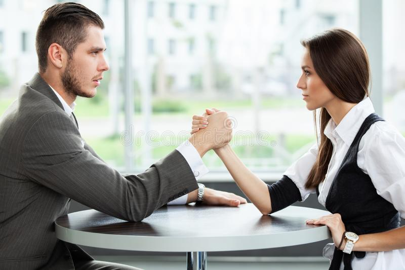 Business and office concept - businesswoman and businessman arm wrestling during meeting in office. Business and office concept - businesswoman and businessman stock image