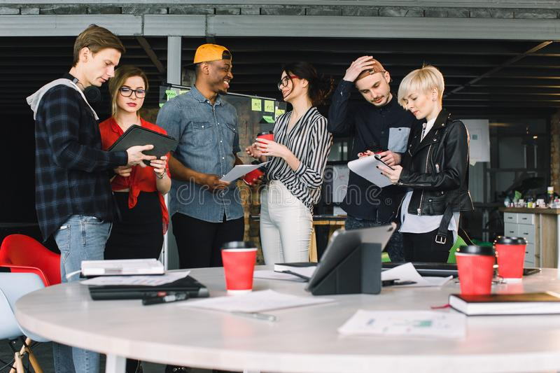 Business Office Connection Contemporary Working Concept. Group of six coworkers in casual wear drinking coffee and. Discussing at the meeting stock image