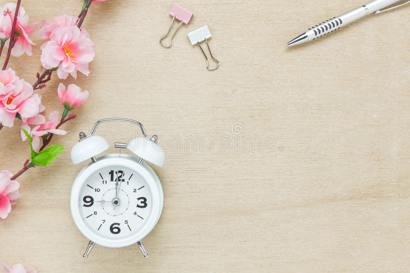 Business office desk background.The silver pen coffee b. Top view business office desk background.The silver pen coffee beautiful pink flower wood white clock on stock photo
