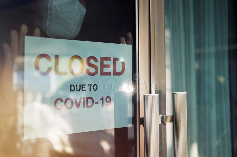 Business office or store shop is closed/bankrupt business due to the effect of novel Coronavirus COVID-19 pandemic. Unidentified. Person wearing mask hanging stock photography