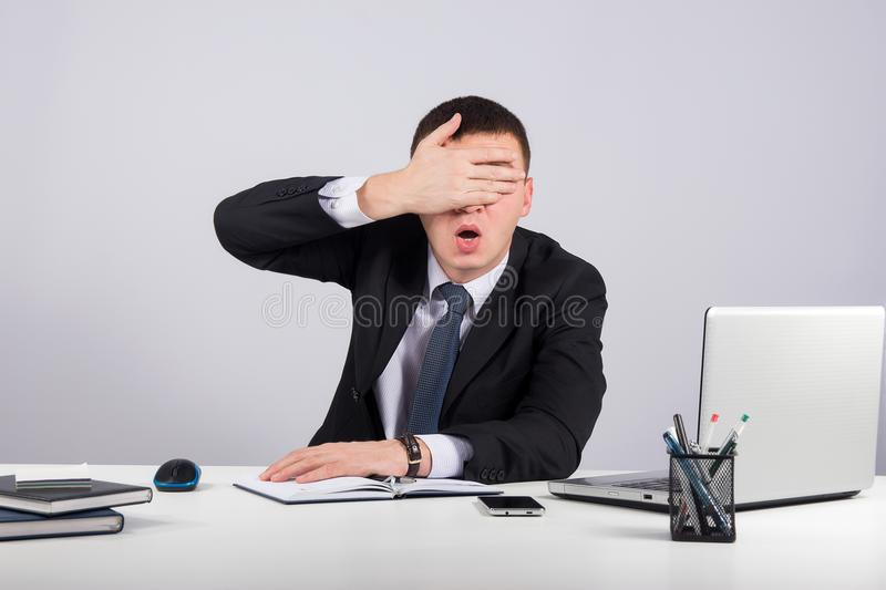 Frustrated businessman close his eyes by hand on gray background royalty free stock photo