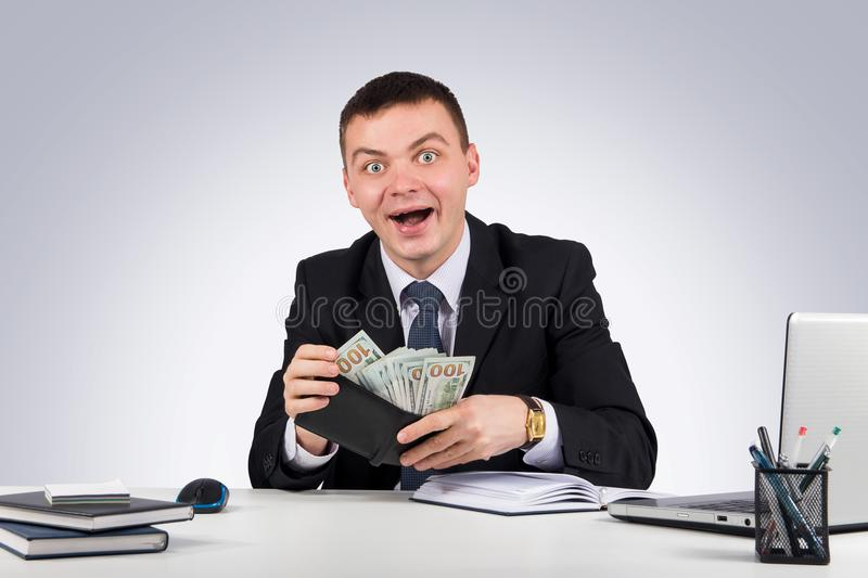 Funny young screaming successful caucasian businessman in black suit holding money stock images