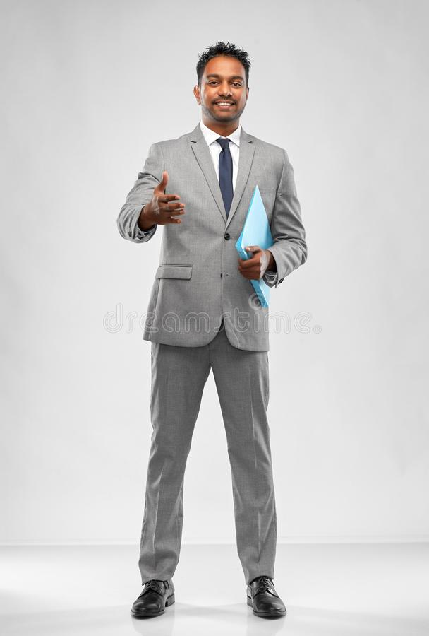Indian businessman stretching hand for handshake. Business, office worker and people concept - smiling indian businessman with folder stretching hand out for stock photos