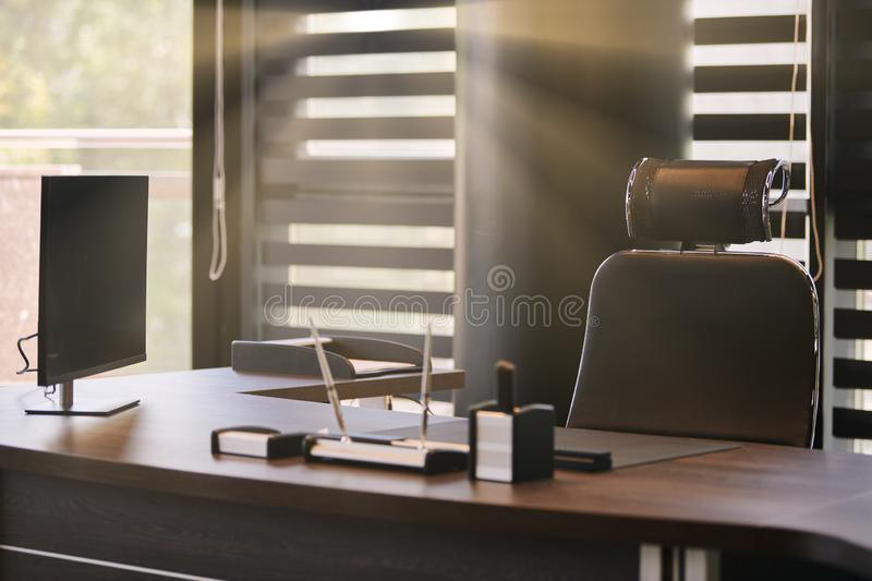 Business office workplace. Sunlight at work place for chief, boss or other employees. Table and comfortable chair. Light through. The half open blinds stock photo