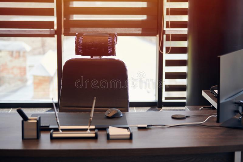 Business office workplace. Work place for chief, boss or other employees. Table and comfortable chair. Light through the half open. Blinds stock image