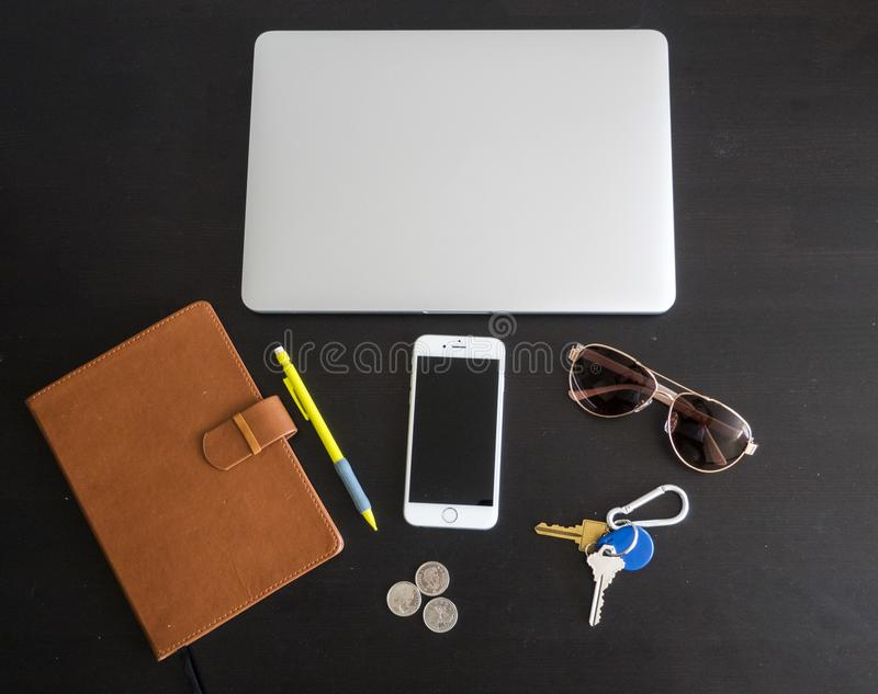 Business office workspace with Various items isolated on a black desk background. Including glasses, keys, laptop, cellphone, journal, pencil and spare change royalty free stock images