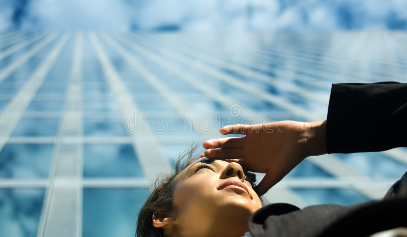 Business Outlook. A young professional woman looking far away in front of a modern office building, presumably at new career options stock images