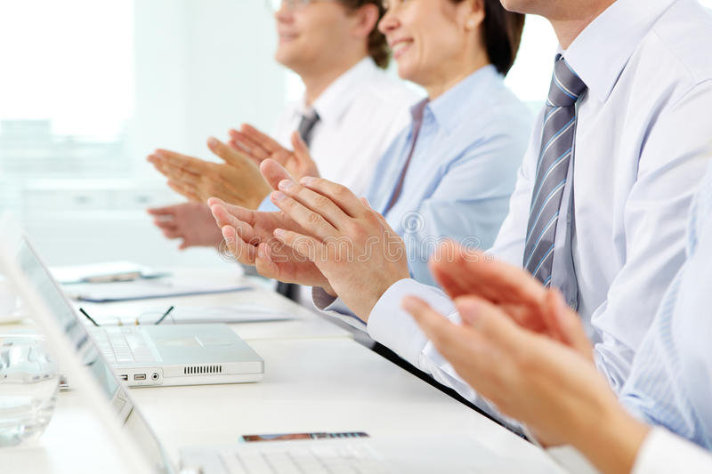 Business ovation. Business people sitting in a row applauding cheerfully to their successful colleague stock images