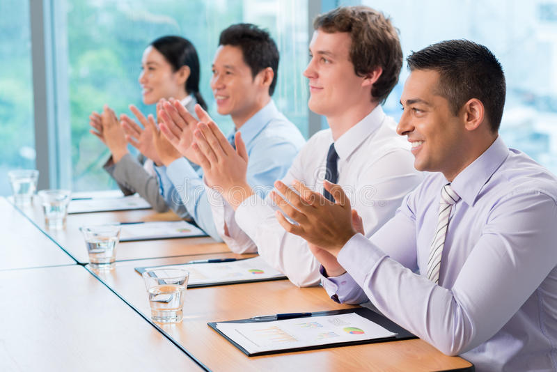 Business ovation. Image of business colleagues applauding in the end of the conference sitting in a line stock photo
