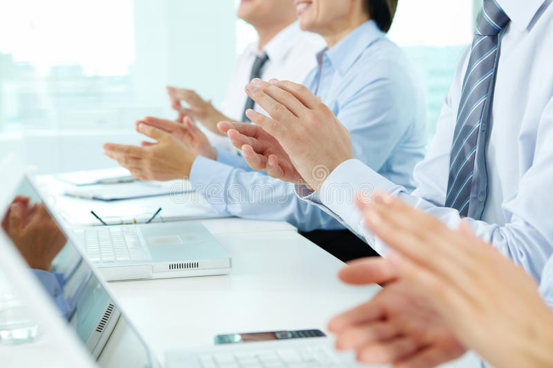 Business ovation. Business people sitting in a row applauding to their successful colleague royalty free stock image