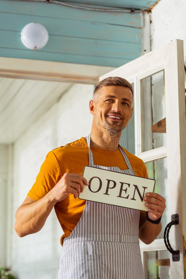 Happy smiling man opening his new shop. stock photo