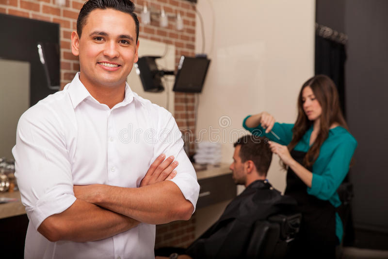Business owner in his shop. Handsome young barber shop owner smiling and managing his business royalty free stock photography