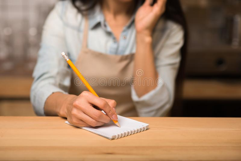 Business owner taking notes. Small business owner taking notes while working in cafe with blurred background royalty free stock photo