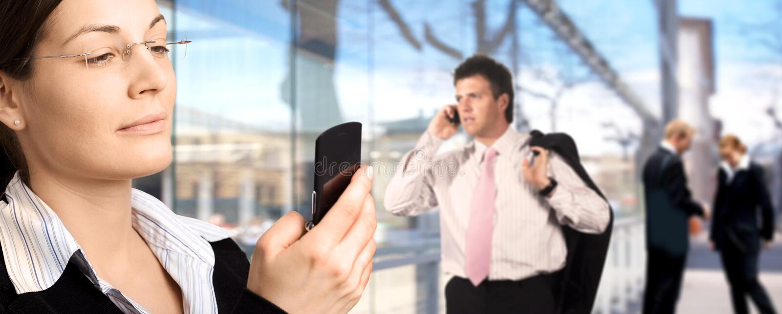 Business panorama. Businesspeople are calling on mobiles in front of a modern office building