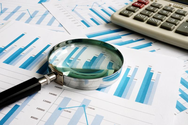 Business papers with financial report and magnifying glass. Audit stock photo